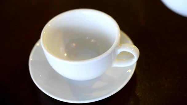 hot aromatic black fruit tea is poured from the kettle into a white cup