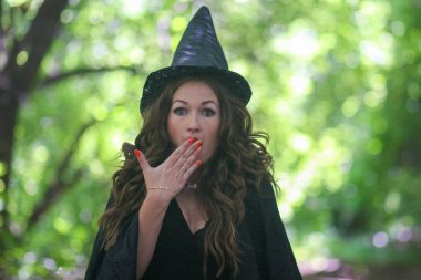 a fairy in a hood and a cloak among the forest. surprise. closes his mouth with surprise