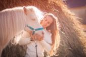 szép lány és egy ló a nap. pozitiv fotó.