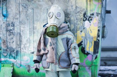 nuclear winter. a small child in a gas mask from a chemical attack. chemical protection mask