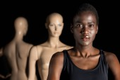 Fotografie attractive young african american woman looking at camera while standing near dummies on black