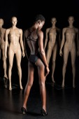 Fotografie back view of stylish african american woman in bodysuit standing in front of mannequins on black
