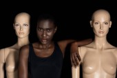 Fotografie attractive young african american woman in bodysuit standing between mannequins and looking at camera on black