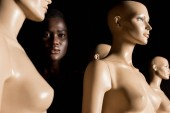 Fotografie attractive african american girl standing between dummies and looking at camera on black