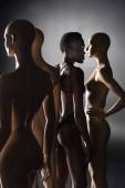 Fotografie young african american model in bodysuit standing between dummies on black
