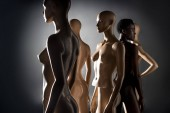 Fotografie african american woman in swimsuit standing between dummies and looking away on black