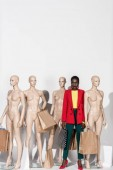 Fotografie stylish african american girl looking at camera while standing between mannequins with shopping bags