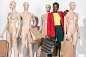 Fényképek stílusos afro-amerikai lány mosolyogva kamera állva között mannequins a bevásárló szatyrok