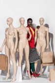 Fotografie beautiful stylish african american girl looking at camera while standing between mannequins with shopping bags on white