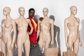 Fotografie attractive stylish african american girl looking at camera while standing between dummies with paper bags on white