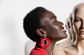 Fotografie side view of smiling african american woman with closed eyes near dummies on white