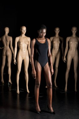 full length view of beautiful young african american woman in swimsuit standing in front of mannequins and looking down on black