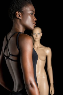 side view of african american girl in swimsuit looking away while standing near mannequin on black