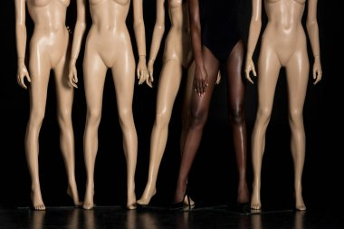 low section of african american girl in bodysuit standing between mannequins on black