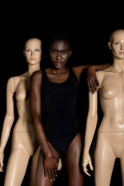 attractive african american girl in bodysuit standing between mannequins and looking at camera on black