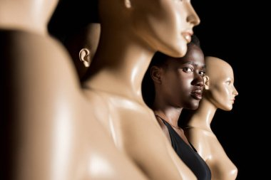 selective focus of beautiful african american girl looking at camera while standing between dummies on black