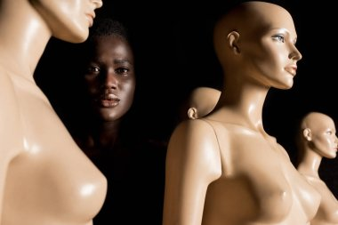 attractive african american girl standing between dummies and looking at camera on black