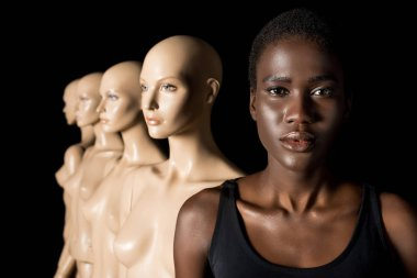 serious african american girl looking at camera while standing with dummies on black