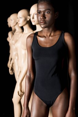 serious african american girl in bodysuit standing in row with mannequins on black