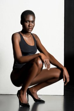 beautiful stylish african american girl in leotard crouching and looking at camera in studio