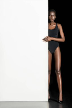 young african american woman in bodysuit standing with blank white card and looking at camera