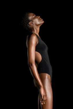 side view of beautiful young african american woman in swimsuit posing with closed eyes isolated on black