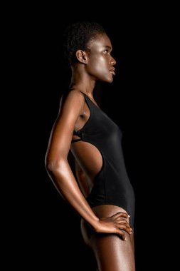 side view of beautiful young african american woman in swimsuit looking away isolated on black