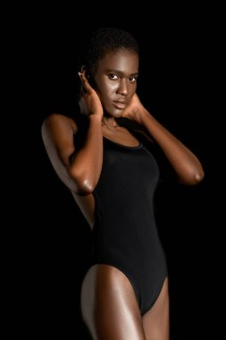portrait of beautiful african american girl in swimsuit looking at camera isolated on black