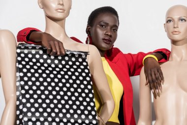 young fashionable african american woman holding shopping bag and looking at camera while leaning at dummies on white