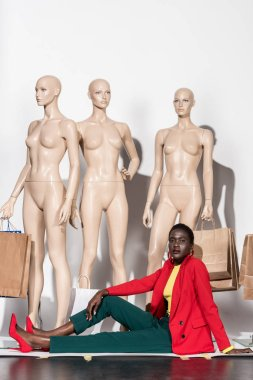 fashionable african american woman looking at camera while sitting in front of mannequins with shopping bags