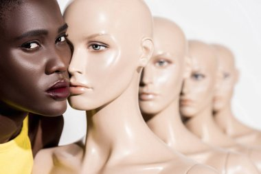 young african american woman looking at camera while standing near mannequins on white