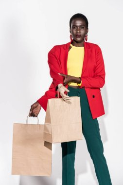 african american woman with hand on mannequin and shopping bags on white