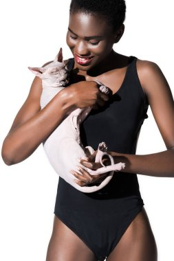 beautiful smiling african american girl in bodysuit holding sphynx cat isolated on white