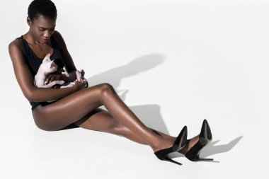 high angle view of beautiful african american woman in leotard and high heeled shoes sitting and holding cat on white