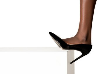 close-up view of female leg in stylish high heeled shoe on white