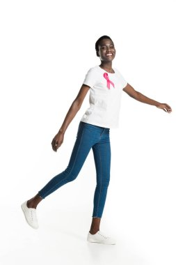 cheerful african american woman with pink ribbon on t-shirt walking and smiling at camera isolated on white, breast cancer concept