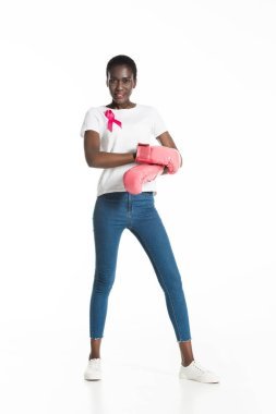 full length view of young woman with pink ribbon wearing boxing gloves and smiling at camera isolated on white, breast cancer concept