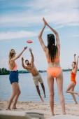 Happy mladých lidí hrát s létající disk na písečné pláži