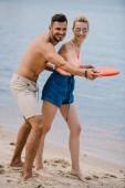 Fotografie glückliches junges Paar mit fliegenden Scheibe am Sandstrand spielen