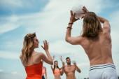 Fotografie nízký úhel pohledu mladých mužů a žen přátel hrát volejbal na pláži