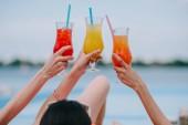 Schnappschuss von jungen Freundinnen mit Gläsern mit Sommercocktails am Strand