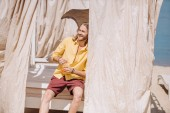 krásný usměvavý mladý muž držení sklenice koktejl při posezení v bungalovu na pláži
