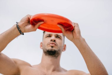 low angle view of handsome young man holding flying disk