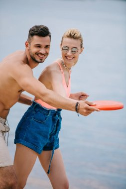 happy young couple playing with flying disc on beach
