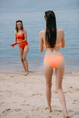 young women in swimwear playing with flying disc on sandy beach