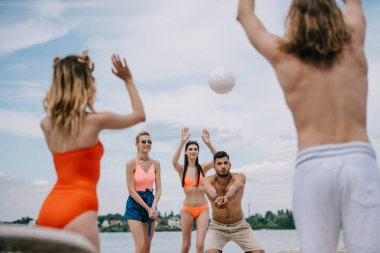young people playing with ball on beach