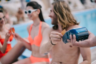 smiling young man paying with credit card and looking at female friends drinking champagne at pool