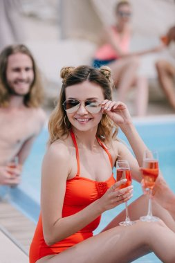 happy young woman in swimsuit and sunglasses holding champagne and smiling at camera at poolside