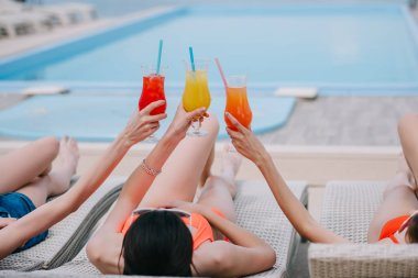 girls lying on chaise lounges and holding glasses with summer cocktails at poolside