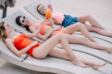 happy female friends in swimwear and sunglasses resting with cocktails on chaise lounges